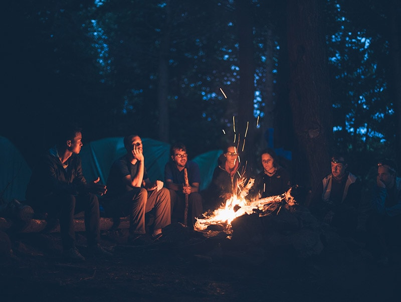 Group of RV renters sitting around a campfire.