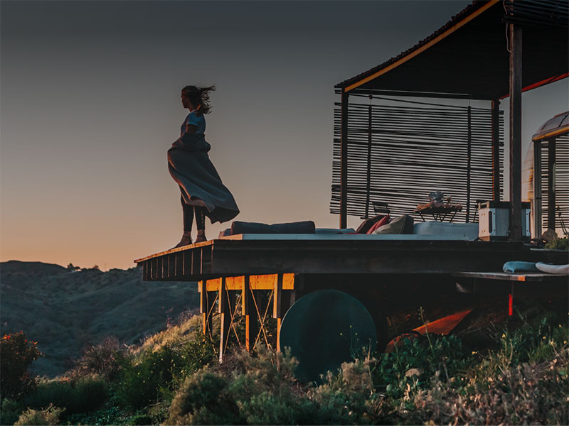 A woman standing on a deck looking into the sunset.